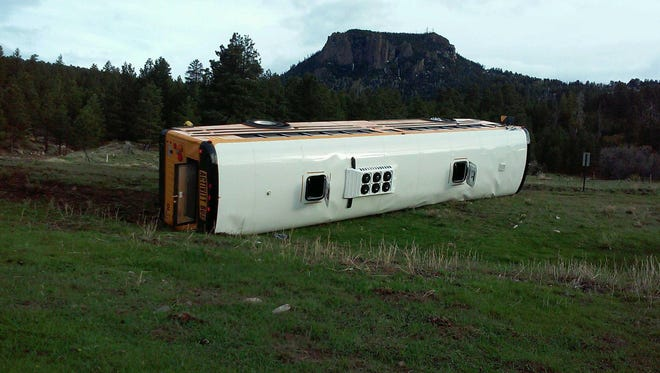 A Farmington Municipal School District bus lies on its side on Indian Route 13 near Red Valley, Ariz., after a rollover crash on May 4, 2015. The bus was transporting 44 Bluffview Elementary School students and two staff members on a field trip when the driver lost control.