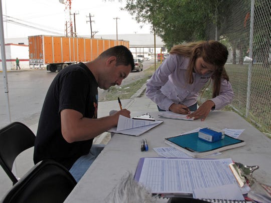 """In this April 28, 2017 photo, Aimee Gomez, a recruiter for """"maquiladora"""" assembly plants in Reynosa, Mexico helps Juan Luis Alvarado de la Rosa fill out a job application in an industrial park, across the border from McAllen, Texas. President Donald Trump has said NAFTA was """"a catastrophic trade deal for the United States,"""" but the reality is far more complicated, especially at the border where communities are enmeshed in a shared economy."""