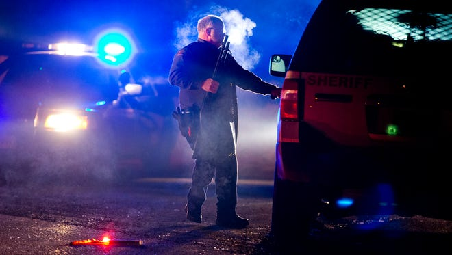 A Oregon State police officer stands by a vehicle as police block Highway 395 in Seneca, Ore., late Jan. 26, 2016. Authorities said shots were fired during the arrest of members of an armed group that has occupied a national wildlife refuge in Oregon for more than three weeks.