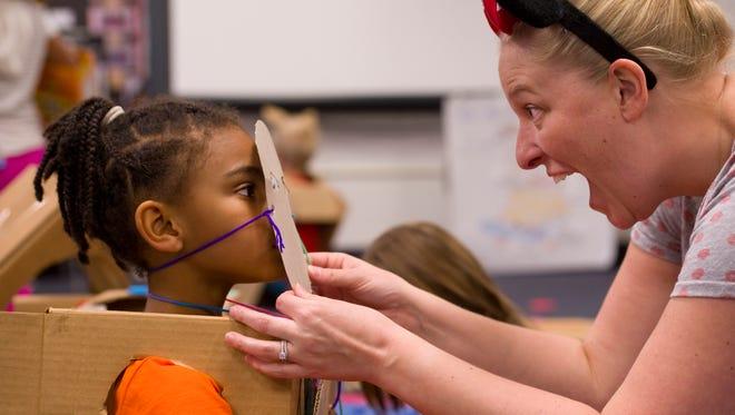 Art teacher Rachel Walker helps kindergartner Brooklyhn Scott with her cardboard mask before the Delaware Elementary School parade of cardboard costumes Monday afternoon. The kids had created their own cardboard costumes as part of a STEM-based global Cardboard Challenge.