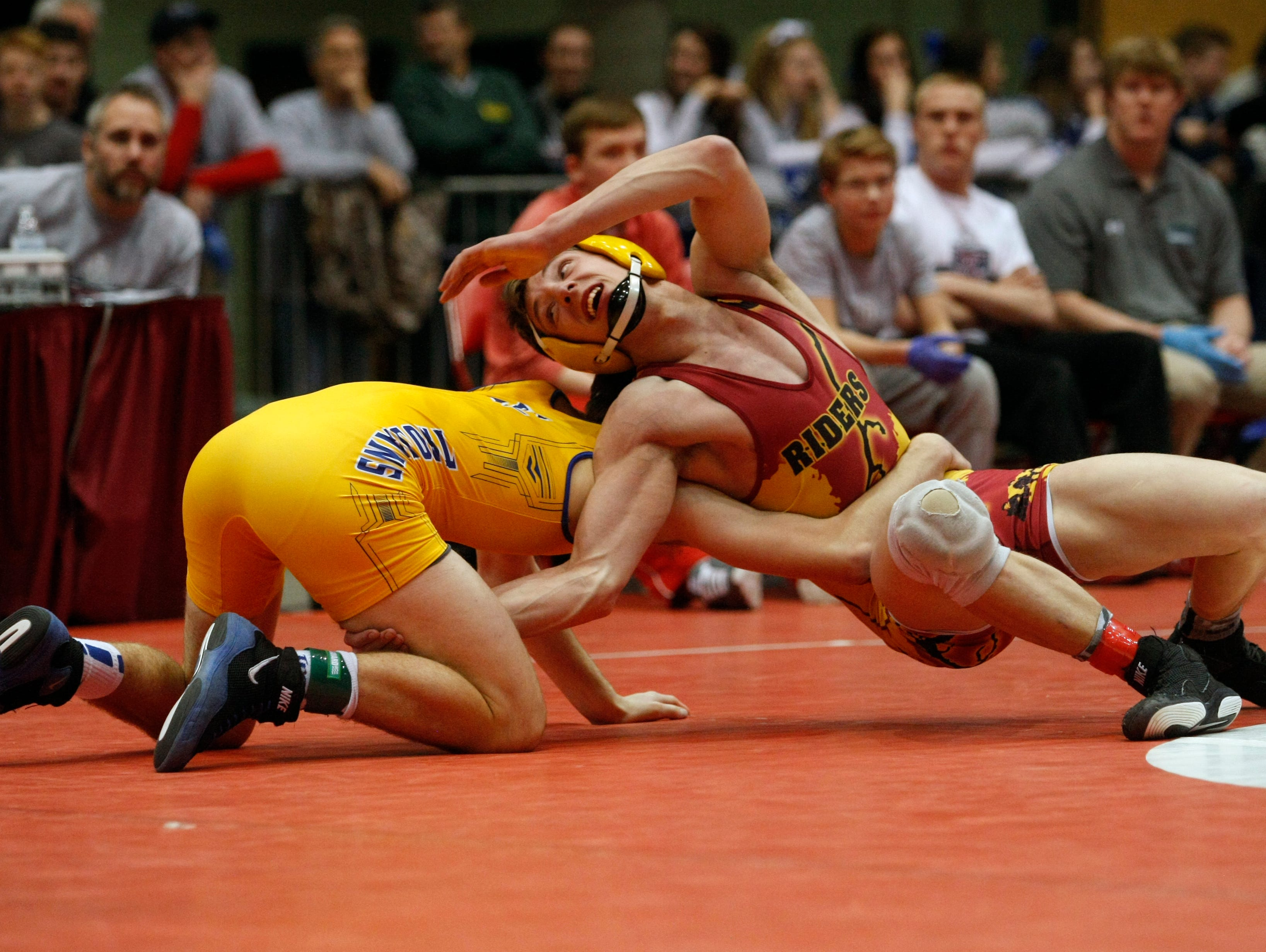 Carter Lohr, Sioux Falls Roosevelt, reverses Austin Ideker, of West Central, during the state championship match at 138 pounds Saturday night in Rapid City. Lohr defeated Ideker 5 – 4.