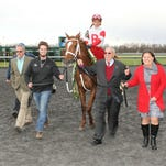 Ken Ramsey walks Oscar Nominated to the winner's circle at Turfway Park after the colt's score in the Spiral Stakes.