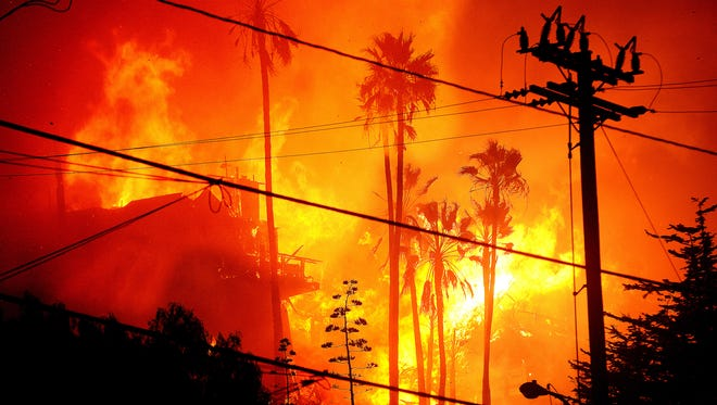 Flames rose 60 feet above the Hawaiian Village apartments in Ventura when the city was struck by the Thomas Fire in early December. The United Way is distributing $1,500 to people whose homes were destroyed or suffered major damage in the fire.