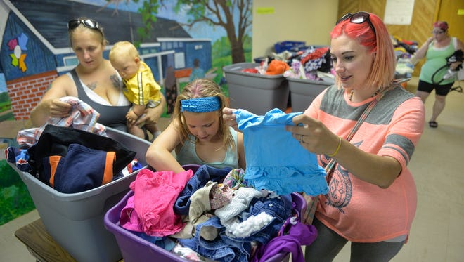 Friends Jennifer Schneider, left, of St. Cloud, and Angela Stenman, right, of Sartell, look through tubs of clothing to fit their children Saturday at the Promise Neighborhood's back-to-school event. With them are Schneider's son, Dahlton, 7 months., and Stenman's daughter, Calie, 11. The event offered a lunch, school supplies, clothing, informational booths, art and other activities for families.