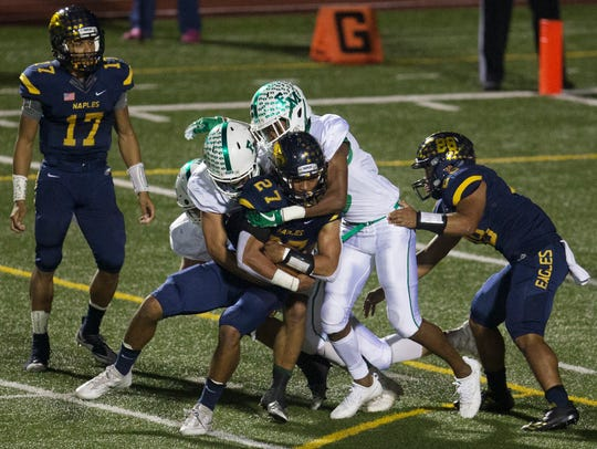 Naples High School's Cesare Mellusi is tackled for