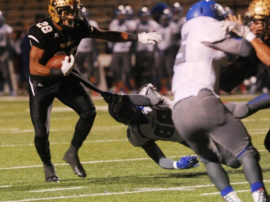 Abilene High running back Abram Smith pulls away from an El Paso Americas tackler during the Eagles' 55-0 area-round win Friday, Nov. 18, 2016 at Shotwell Stadium.