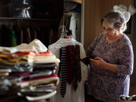 Donna Manning sorts through clothes from her late husband,