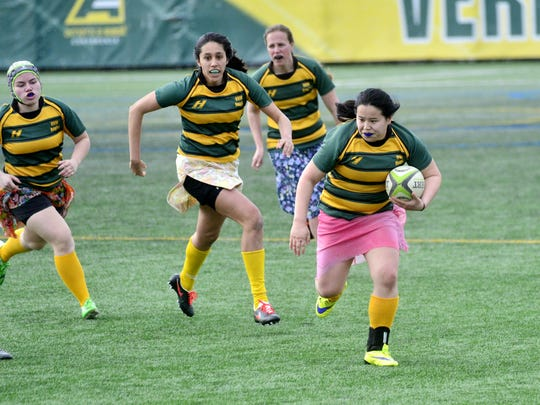 A University of Vermont women's rugby player Rebecca Paige, right, runs with the ball down the field during the annual prom dress game on Sunday, April 9, 2017, in Burlington.