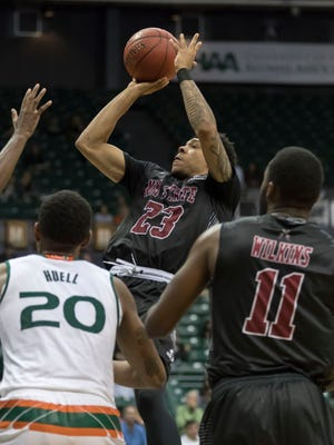 New Mexico State guard Zach Lofton (23) shoots as forward Johnathon Wilkins (11) and Miami forward Dewan Huell (20) watch during the second half of an NCAA college basketball game at the Diamond Head Classic tournament, Saturday, Dec. 23, 2017, in Honolulu. New Mexico State upset Miami, 63-54.