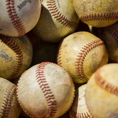 A bucket of baseballs sits on the field during game