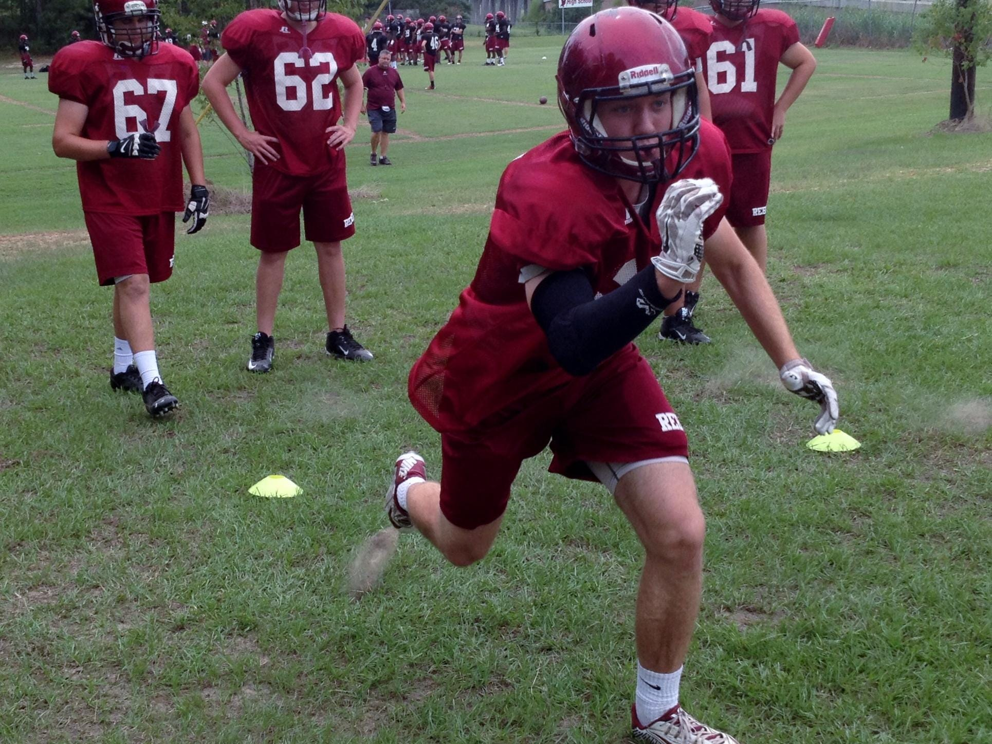 Pineville senior right tackle Harrison Nugent (64) runs through a drill during practice Tuesday. The undersized Nugent is one of the top academic and most involved students at Pineville High School.