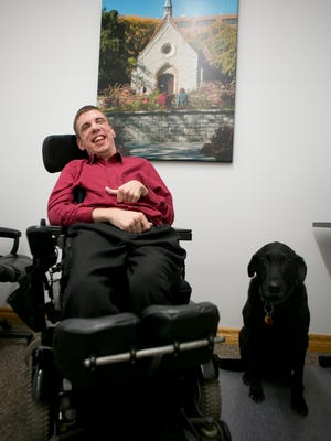 Andy Thain, founder and chairman of At Home Care, poses with his dog, Louie, in his office in Thorp, Friday, April 3, 2015.