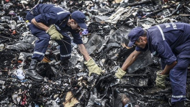 Ukrainian State Emergency Service employees search for bodies among the wreckage at the crash site of Malaysia Airlines Flight MH17 in the region of Donetsk on July 20, 2014.