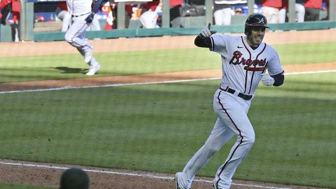 Atlanta Braves' Cristian Pache, rear left, heads home to score the winning run as Braves' Freddie Freeman celebrates heading to first after hitting an RBI single to beat the Reds 1-0 in 13 innings in Game 1 of a National League wild-card baseball series, Wednesday, Sept. 30, 2020, in Atlanta.