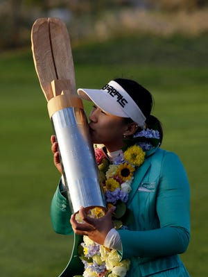 Amy Yang of South Korea kisses her trophy after winning the KEB HanaBank Championship golf tournament.