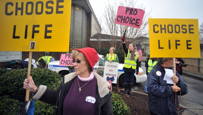 People supporting and opposing abortion access demonstrate outside of the Alabama Women's Center for Reproductive Alternatives in Huntsville, Ala., Feb. 23, 2013, which later had to close its doors.