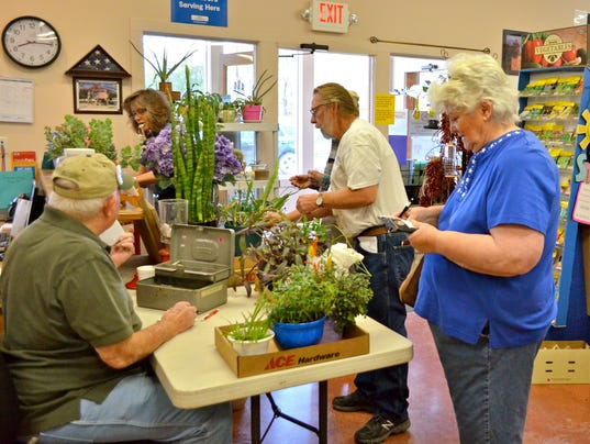 Gerald-Garrett-Bill-Jeffrey-and-Debbie-Myers-working-the-2016-plant-sale-and-Sally-Moore-purchasing-plants.JPG