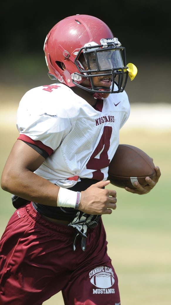 Running back BJ Smith carries the ball during football