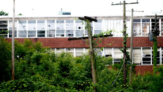 Underbrush begins to take over utility poles as the A.K. Stewart Science Bldg begins falling into disrepair on the Knoxville College campus in Knoxville, Tennessee on Friday, June 1, 2018.