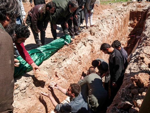 Syrians dig a grave to bury the bodies of victims of