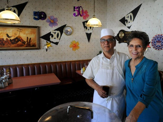 JOSEPH A. GARCIA/THE STAR 'It's the customers that keep you going,' commented Christopher Castillo (left), chef at the Vagabond coffee shop and restaurant in Ventura, who said he has been working there 46 years. Castillo and Vagabond owner Jolene McBee (right) stand near decorated walls as the business celebrates its 50th year.