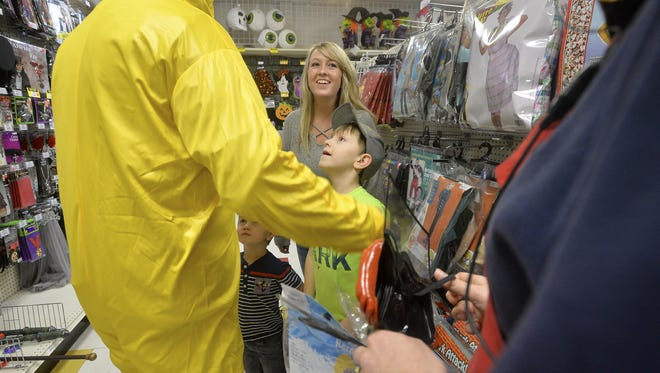 Gray Chagnon tries on a hazmat suit halloween costume as his wife, Ashlee, and sons Carter and Gannon look on while costume shopping at Party America on Friday afternoon.