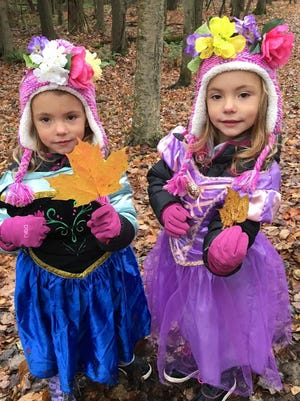 "Girls donning princess costumes and nature crowns show two different leaves Saturday during Woodland Dunes' ""Be a Nature Princess"" program."