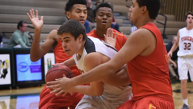 Douglas' Tanner Williams is surrounded by Jesuit's, clockwise, Isaiah Rutherford, Armoni Rivers and Malik Duffy as he attempts to shoot during Thursday's game at the Wild West Shootout tournament at Bishop Manogue.
