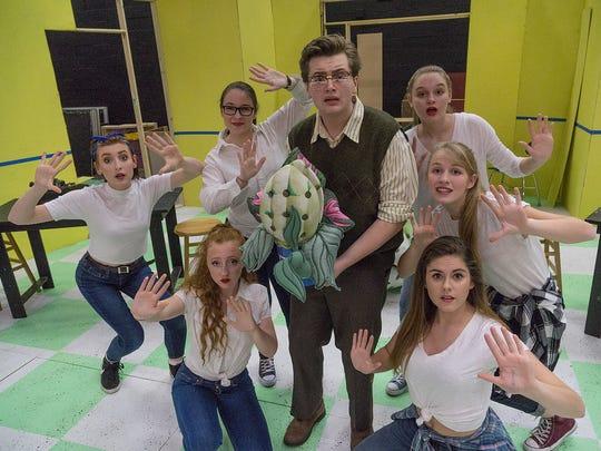 Seymour (Dalton Barthold) holding the mysterious plant Audrey II with the chorus of Ronnette (Elyse Kazmierski) Chiffon (Corinne Marsh, Diana (Amber Mero), Vandella (Amanda Ellen Wood), Crystal (Morgan Gagnon), and Shirelle (Nora Detgen).