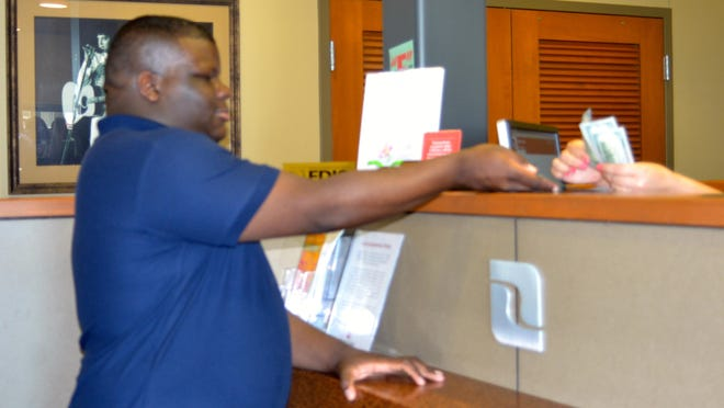 D'Marcus Dumars, 18, received cash from Red River Bank after he and his family poured $1,010 in loose change into a coin-counting machine at the branch on Wednesday. His mother, Deborah Dumars, saved the coins over four years to go toward D'Marcus' graduation trip to Las Vegas. She and son Daniel Jr. will join D'Marcus on the trip that she promised him as a freshman in high school if he graduated.