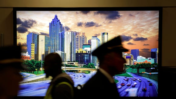 This file photo shows a pilot walking past an image of Atlanta at the city's Hartsfield-Jackson Atlanta International Airport.