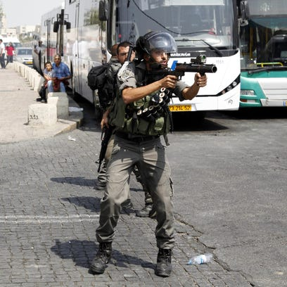 Israeli border policemen aim to fire tear gas during a confrontation with Palestinians after Friday prays outside the Old City in Jerusalem Friday, Oct. 2, 2015.