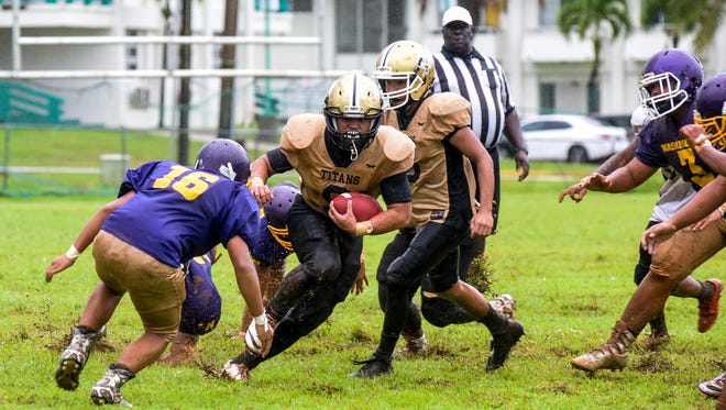 Tiyan High School Titans' Javier Lujan (9) finds an opening in the defensive line of the George Washington High School Geckos during an Interscholastic Football League game at the University of Guam football field in Mangilao on Saturday, Sept. 9, 2017.