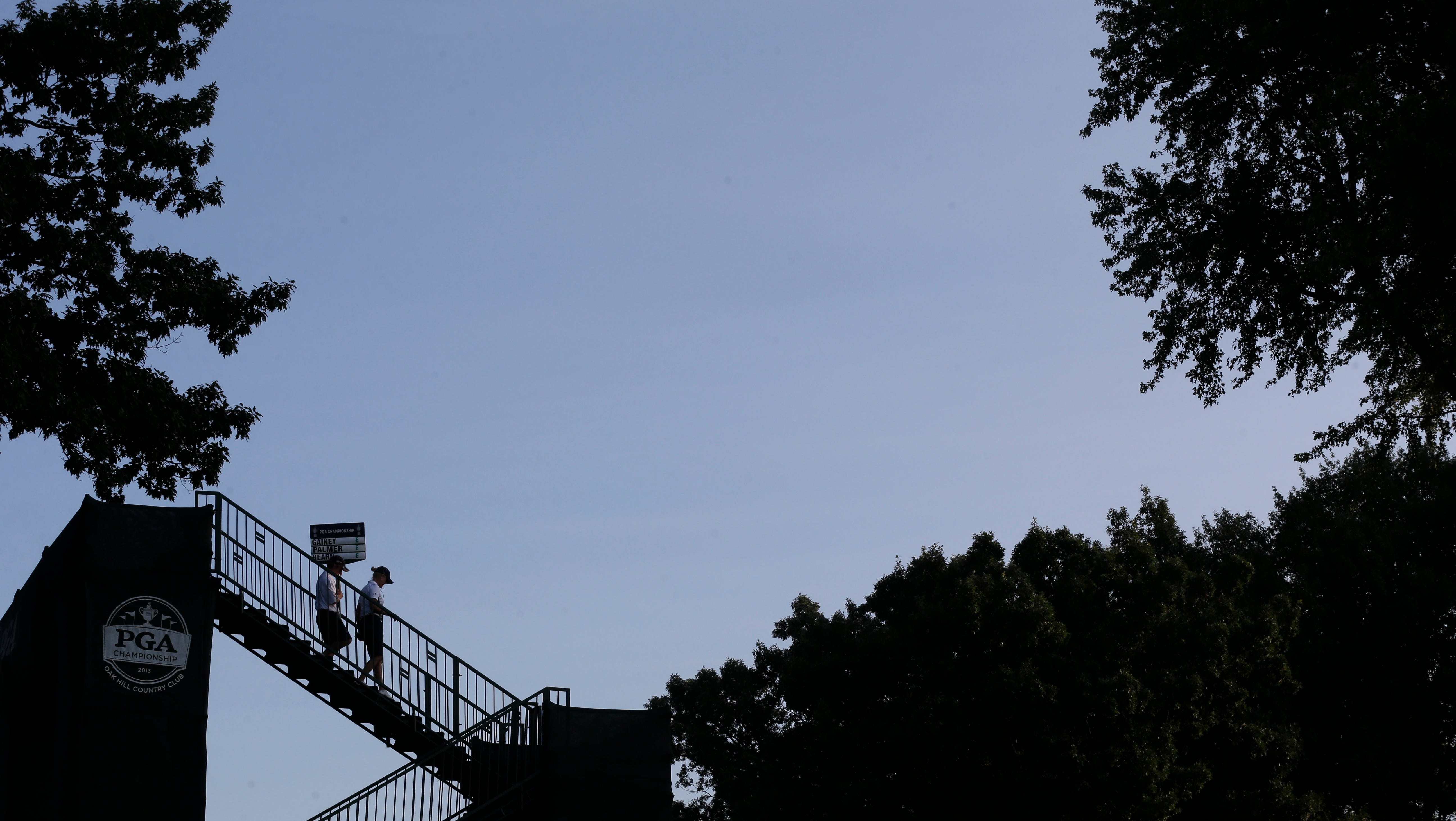 A standard bearer walks to the first tee during the first round of the PGA Championship golf tournament at Oak Hill Country Club.