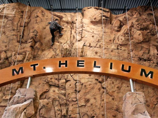 Kids can climb the rock wall at Helium Trampoline Park.