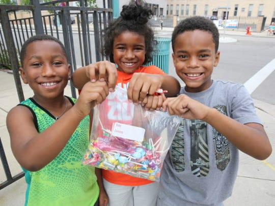 (From left) Derrick Smith 8, Jamere Rogers, 8, and Ralil Rogers show off their bag of candy collected from the LaborFest parade.