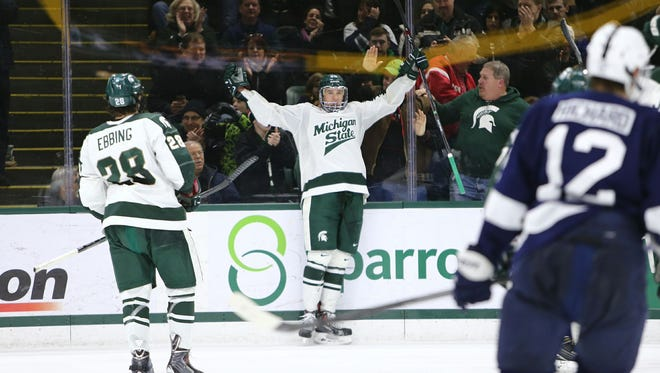 Mackenzie MacEachern raises his arms after scoring his third goal of the game in MSU's 3-2 victory over Penn State on Saturday at Munn Arena in East Lansing. The sophomore's hat trick was the Spartans' first since Matt Berry did it against Michigan on Nov. 10, 2012.