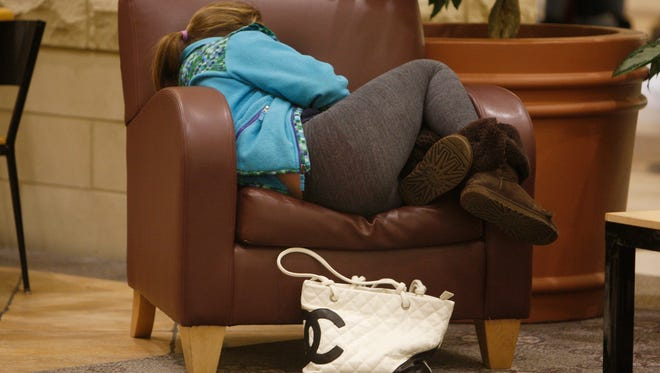 Mia Thomas, 12, of Pittsford gets a some sleep in while other relatives shop.