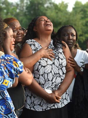 Bendu Chenoweth, mother of Moses Cole, mourns her son's death during a vigil at Falls Park in Sioux Falls, S.D. on Saturday, Aug. 18, 2018.