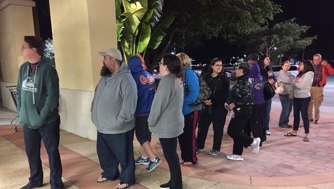 Shoppers wait in line to enter the Sports Authority at the Coconut Point mall on Friday.