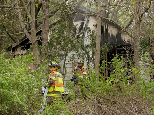 Trumansburg firefighters Devon DeMarco, left, and Matt Muraca stretch a hose line into the house at 1480Taughnnock Blvd, Saturday morning to put out the smoldering remains of a fire. The house caught fire and was almost completely destroyed late Friday afternoon.