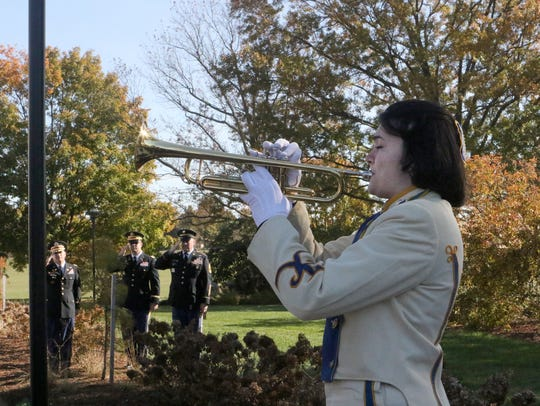Abigail Merritt, a senior in the A.I. DuPont High School Band, plays Taps at the conclusion of the Veterans Day Ceremony held Saturday at Memorial Bridge Plaza in New Castle.