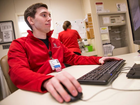 Ryan Page, a registered nurse at Indiana University Health Methodist Hospital, works on a computer in a nurses station on Tuesday, Dec. 19, 2017.