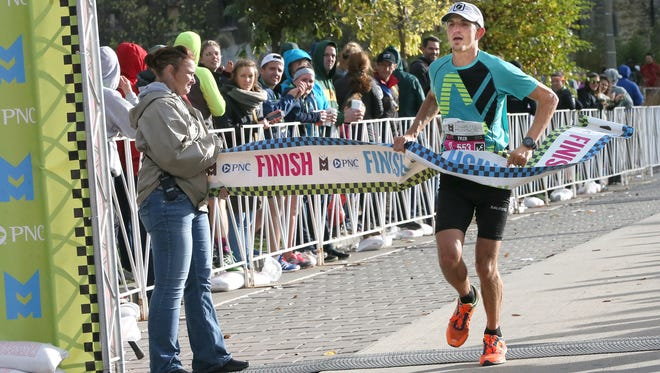 Tyler Sigl of Seymour crosses the finish line to win the PNC Marathon in an unofficial time of 2:20.