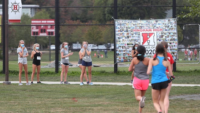 Members of the Hingham High girls cross country team cheer on their teammates as they make their way around the fields.