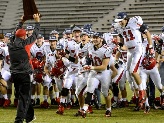 Fyffe's players run to accept the trophy from Fyffe coach Paul Benefield after the 28-17 victory over Elba in the AHSAA Class 2A state championship game at Jordan-Hare Stadium in Auburn on Friday.
