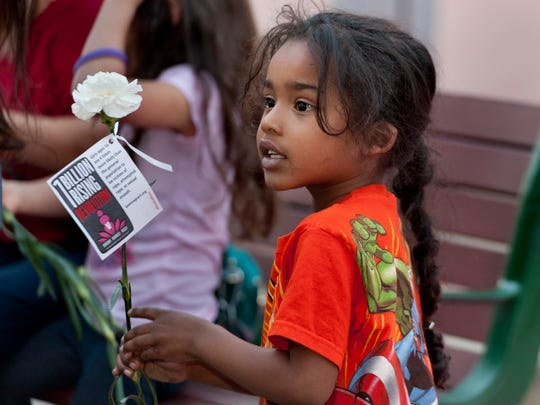 Demorie Dillihunt, 4, holds one of the carnations given out by One Billion Rising supporters during their march along Main Street in Downtown Visalia on Friday.