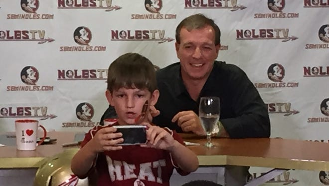 A young Florida State Seminoles fan tries to take a selfie with FSU football coach Jimbo Fisher  during his final radio call-in show of the season on Wednesday, Dec. 2, 2015.