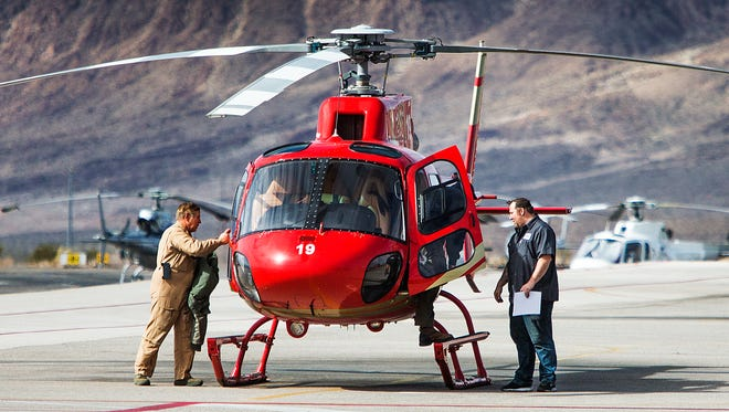 Pilots climb out of  a helicopter at the Papillon Grand Canyon Helicopters Boulder City Terminal in Boulder City, Nevada, after running the engines for about 12 minutes but not taking off, Tuesday, February 13, 2018.  The fleet of tourist helicopters is grounded following the fatal crash of a Papillon helicopter in the Grand Canyon that killed three and critically injured four other, Saturday, February 10, 2018,