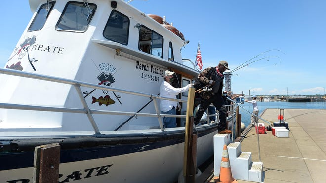 Perch Pirate Captain Bob Zawadzki, left, watches as angler Brian Peek of Pittsburgh leaves the boat Saturday at the East Basin of Dobbins Landing in Erie. The boat just returned from a morning of walleye fishing on Lake Erie.